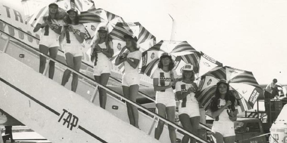 Um grupo de modelos fazem publ i cidade às corridas Martini Racing nas escadas de um avião Boeing B-707 da TA P, em 1976.Foto encontrada em www.sabado.pt - Memórias do Aeroporto d